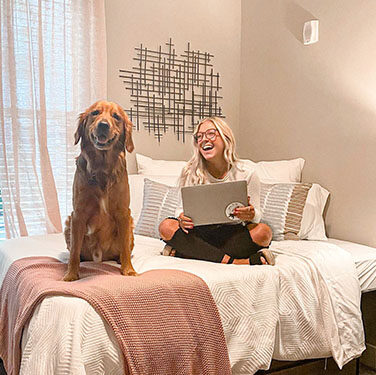 Resident at The Mark Tucson Sitting with her dog in an apartment bedroom